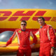 DHL Twister Duo pilots pose in front of their plane, while a rather larger example from the company rests behind.