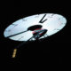 A remote-controlled helicopter, flying at night with the image of a clock projected on the undersides of its rotorblades!