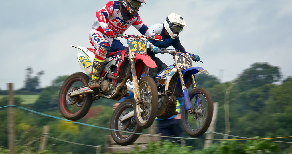 Two riders crest a jump at the motocross track at Woodford, Northants.